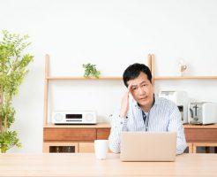 自宅で額を抑える中年男性
