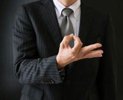 指でお金マークを作っている男性