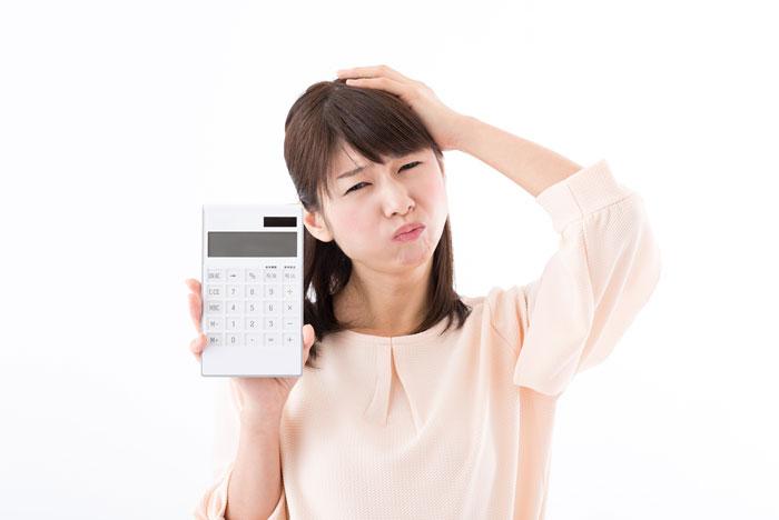 電卓を抱えて悩んでいる若い女性