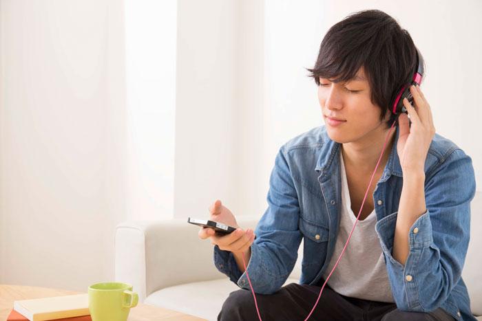 自宅で音楽を聞いている若い男性