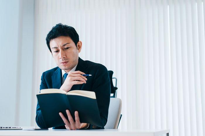 厳しい表情で手帳を見つめる中年男性