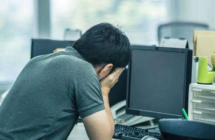 パソコンの前でうなだれている中年男性