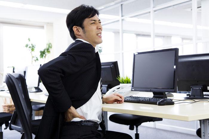 腰を痛めて顔をしかめている男性