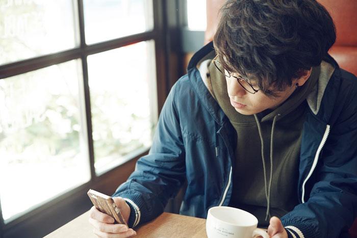 カフェでスマホを操作している若い男性