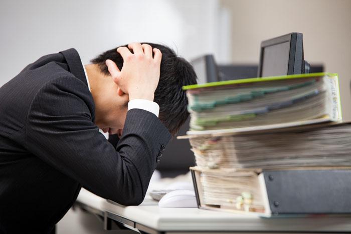 オフィスで頭を抱える男性