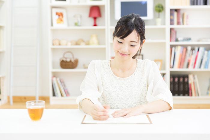 自宅でノートにメモをしている女性