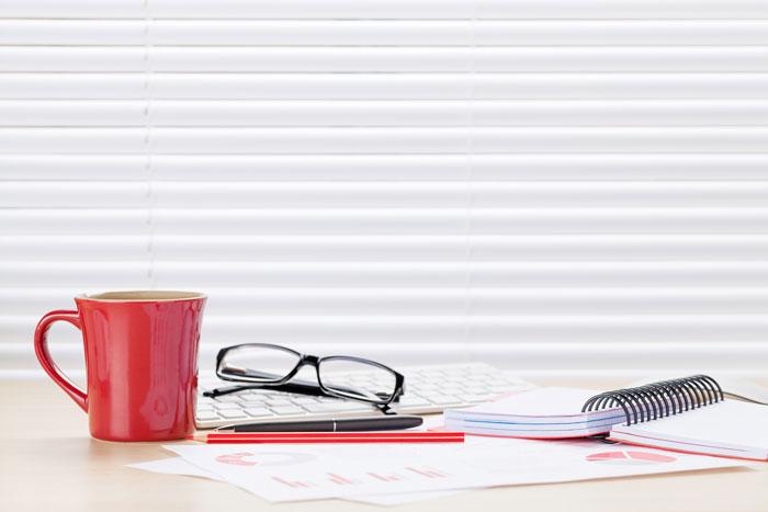 デスクに置かれた眼鏡とマグカップ