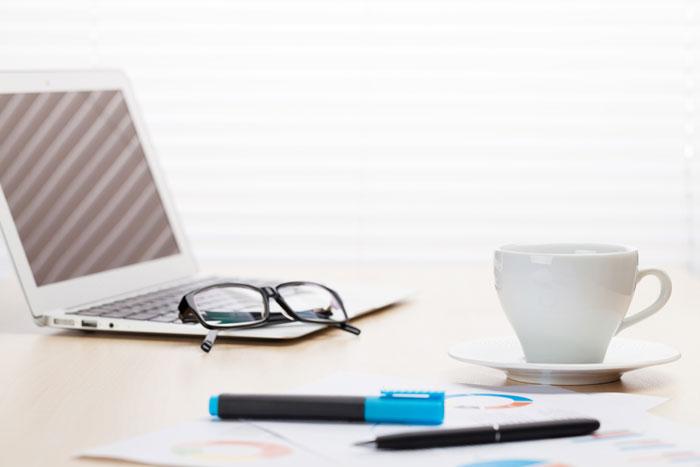 机に置かれたパソコンとコーヒー