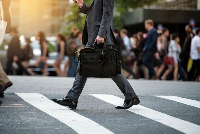 横断歩道を歩くスーツ姿の男性