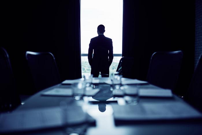 窓から外を眺めている社会人男性