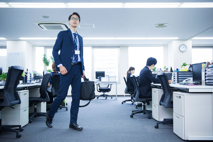 広いオフィスで働くスーツ姿の若い男性