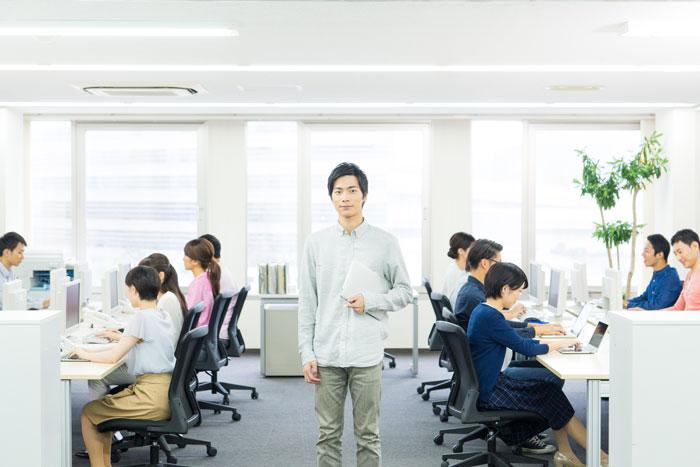 オフィスの真ん中に立つ若い男性