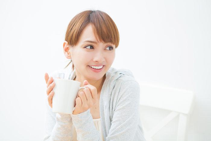 自宅でコーヒーを飲んでいる若い女性