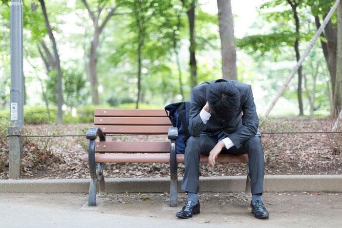 公園のベンチでうなだれている若い男性