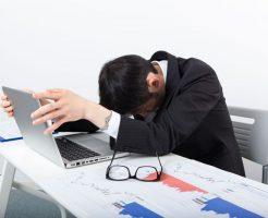 パソコンの前でうなだれている男性