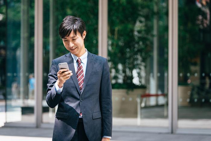 スマホを見ながら歩くスーツ姿の男性