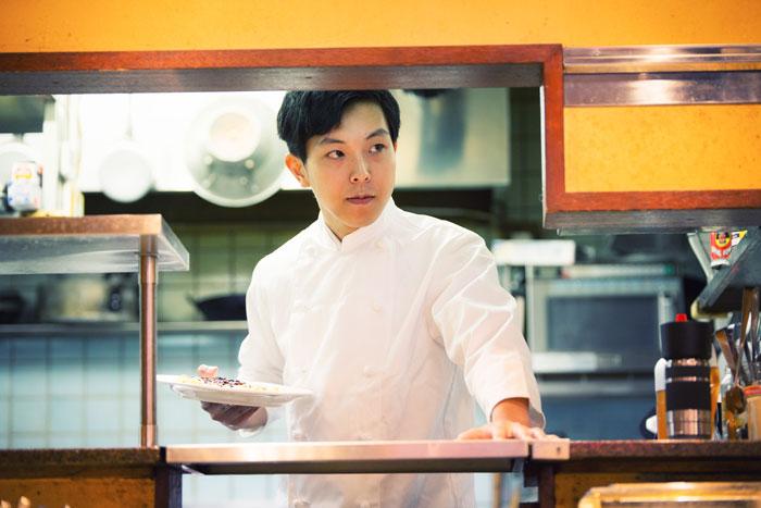 キッチンで働く若い男性
