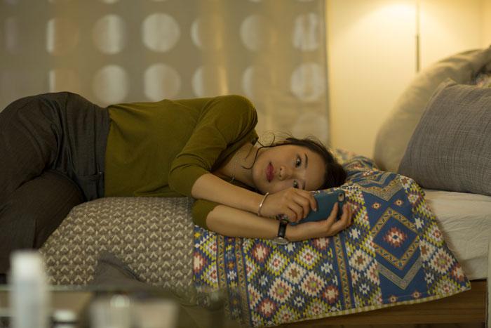 疲れてベッドに寝そべっている若い女性