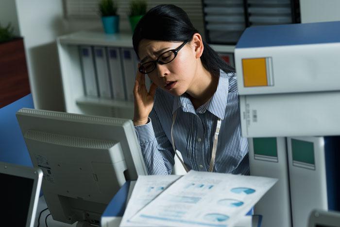 暗いオフィスで頭を抱える若い女性