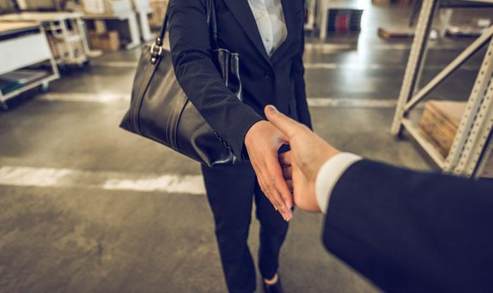 固い握手を交わす若者とベテラン社員