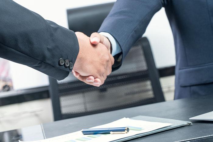 固く握手するビジネスパーソン