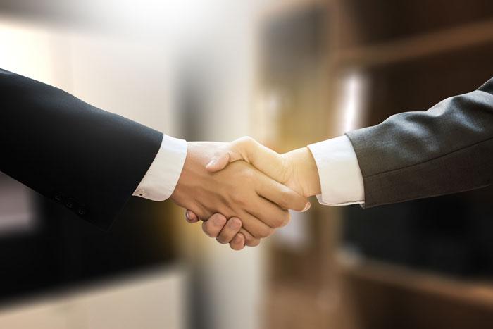 がっちりと固い握手を交わす男性