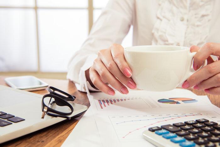 仕事中にコーヒーを飲んでいる女性