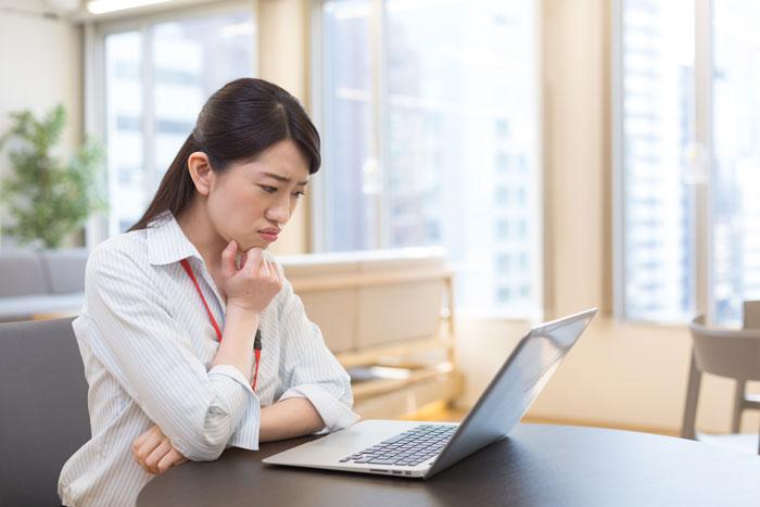 パソコンの前で心配そうな表情をしている女性
