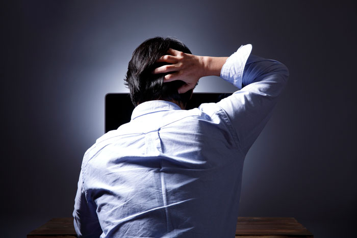パソコンの前で頭を抱える男性
