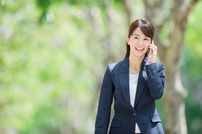 電話をかけながら歩いているスーツ姿の女性