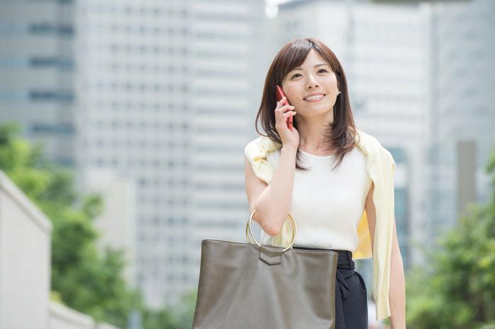 スマホで電話しながら歩く女性