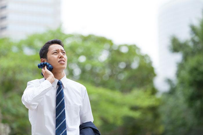 空を見上げるスーツ姿の若い男性