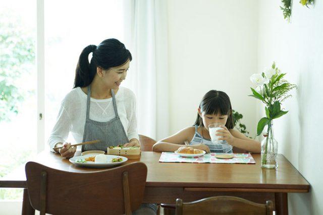 子どもと朝ごはんを食べている母親