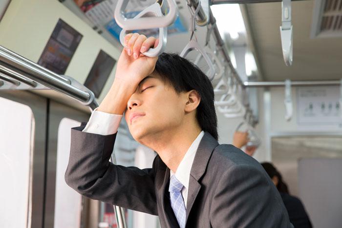 電車で疲れ果てているスーツ姿の男性