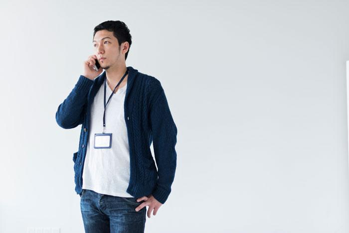 携帯で電話をかけている若い男性