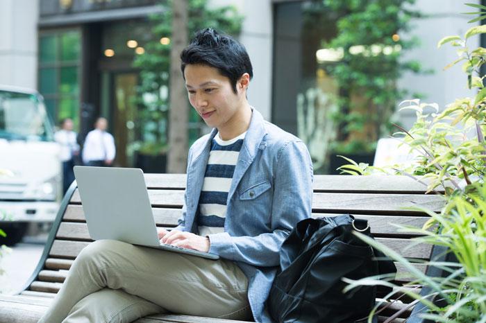 屋外でパソコンを操作している若い男性