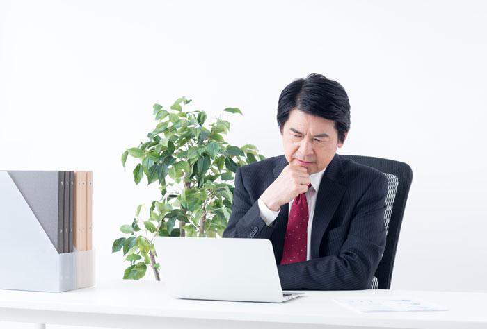 パソコンを睨んでいる中年男性