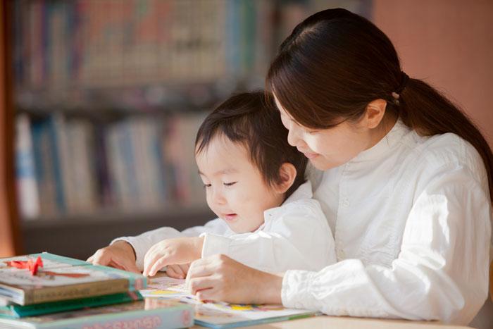 子供と一緒に本を呼んでいる母親