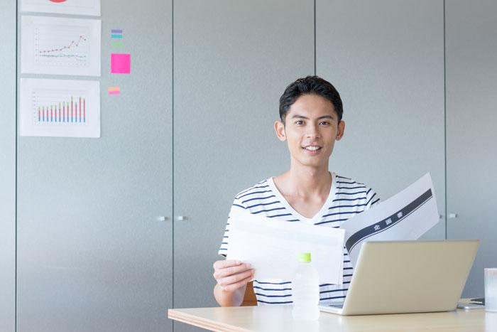 オフィスで書類をチェックしている私服の男性