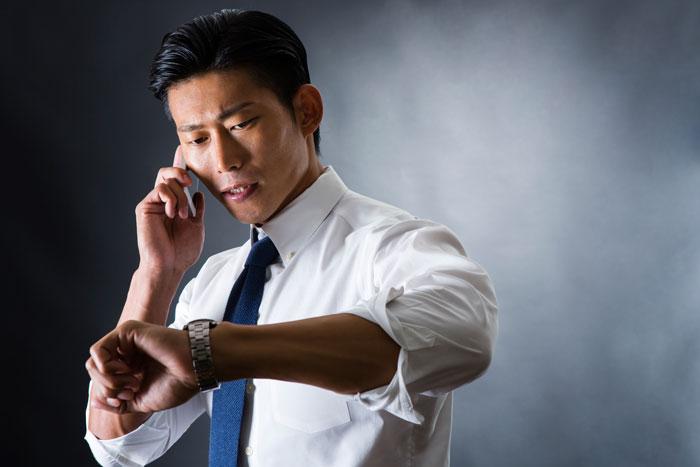 焦って電話中の社会人男性