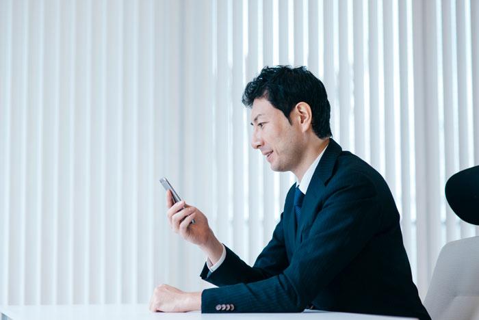 会議室でスマホをチェックする中年男性