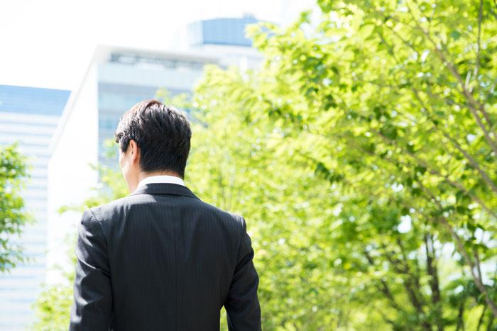 遠くを見つめるスーツ姿の男性
