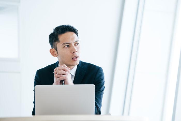 パソコンの前で遠くを見つめる男性
