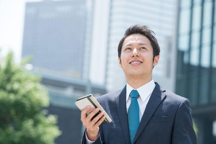 ビジネス街でスマホを持ちながら遠くを見つめる男性