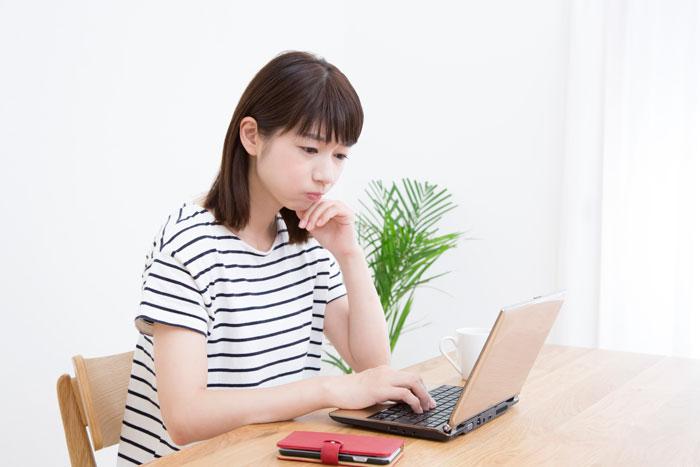 パソコンの前で考え込んでいる女性