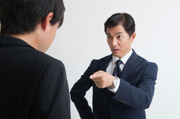 上司に怒られている若い男性