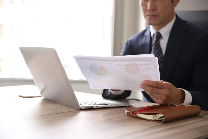パソコンの前で書類をチェックしている男性