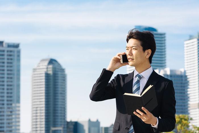 手帳を見ながら電話中の男性