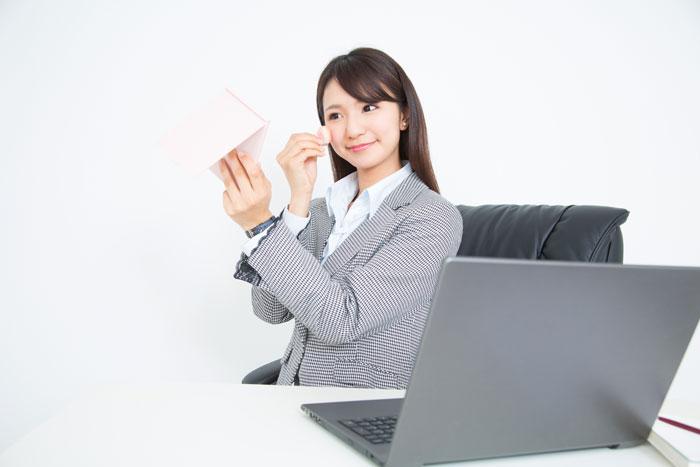 オフィスで化粧中の女性