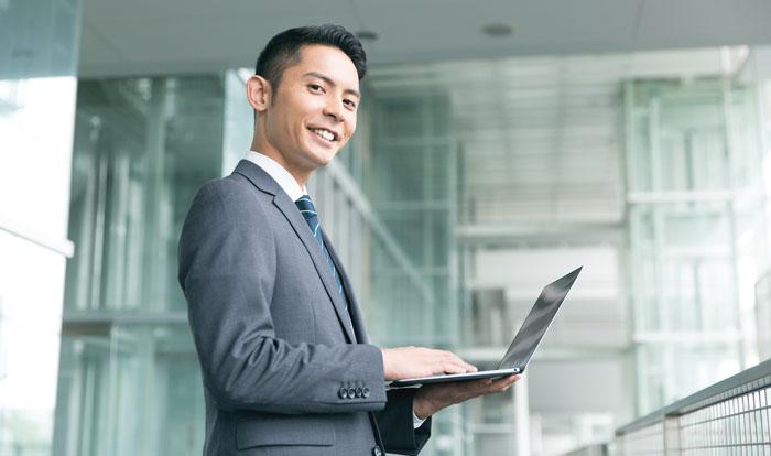 ノートパソコンで仕事中の若い男性